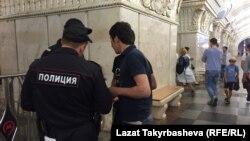 Полиция ходимлари мигрантнинг ҳужжатларини текширмоқда.