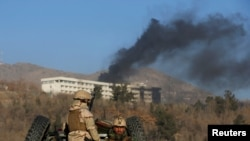 Afghan security forces keep watch as smoke rises from the Intercontinental Hotel in Kabul on January 21.