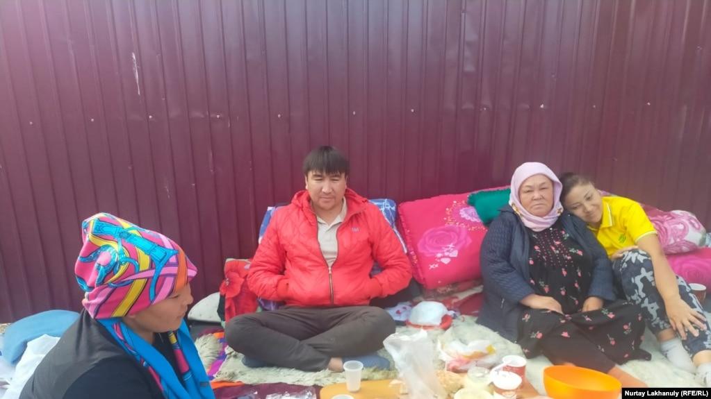 Протестующие сидят возле металлического забора на улице недалеко от здания консульства Китая. Алматы, 14 сентября 2021 года