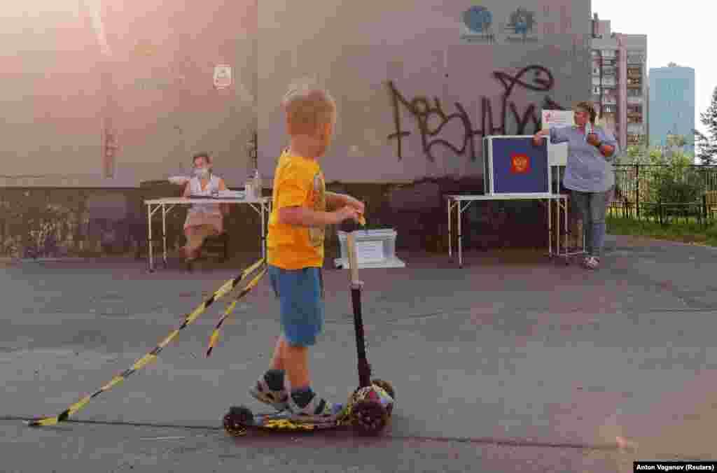 Un băiat pe scuter trecere pe lângă o secție de votare în aer liber din Sankt- Petersburg. Votarea, care a început la 25 iunie, este programată să se încheie la 1 iulie.