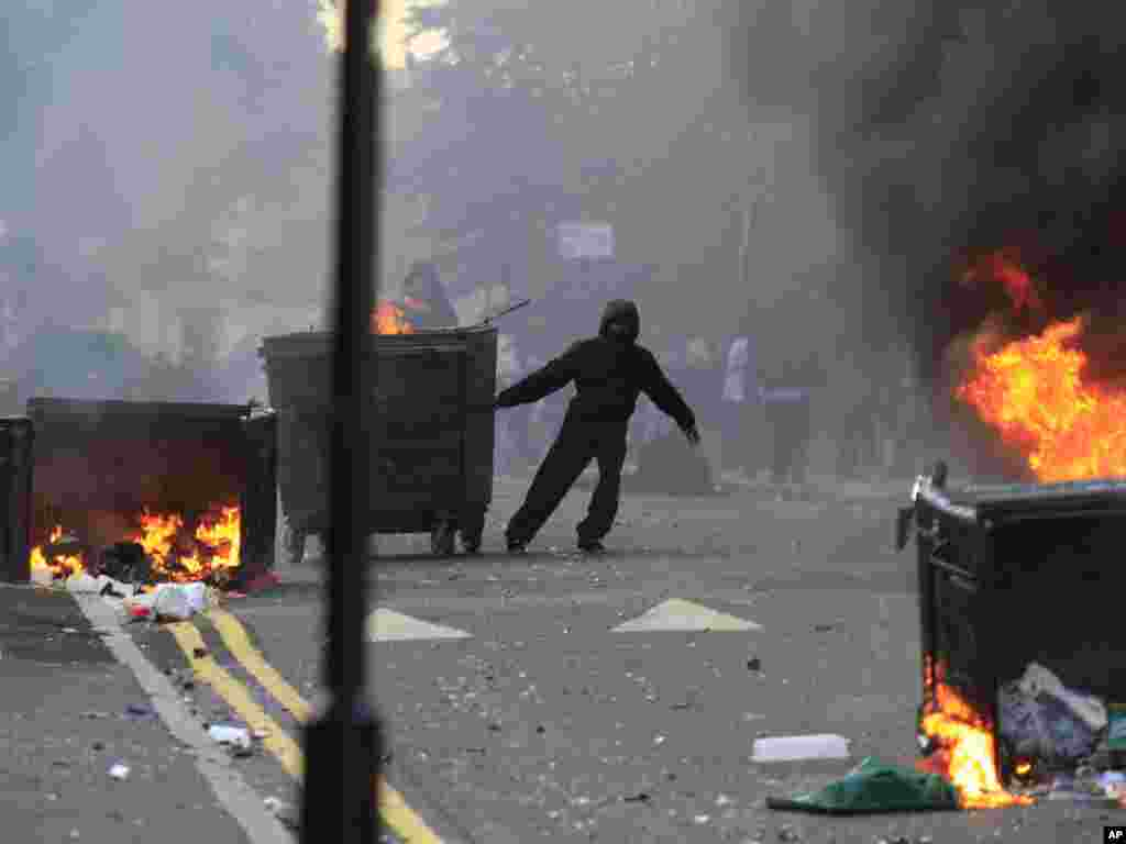 A masked youth pulls a burning garbage bin set on fire by rioters in Hackney, east London, on August 8. Photo by Lefteris Pitarakis for AP