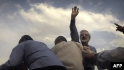 Opposition leader Mir Hossein Musavi waves to supporters during a rally in Tehran just three days after the disputed 2009 vote.