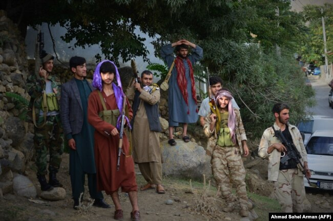 Armed men who have recently joined the fight against the Taliban stand along a road in Bazarak, Panjshir Province, on August 18.