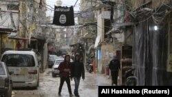 """""""Ислам мемлекеті"""" террористік тобының туы жанында кетіп бара жатқан жастар."""