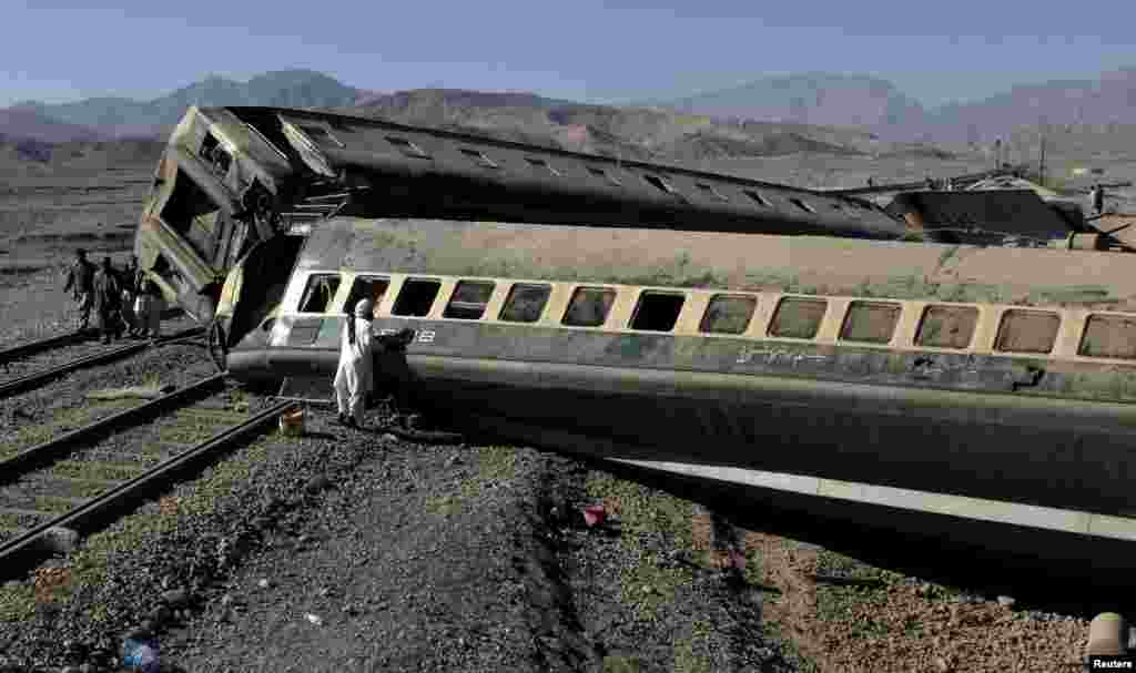 A passenger looks for his belongings after a train derailed in Quetta, Pakistan. (Reuters/Naseer Ahmed)