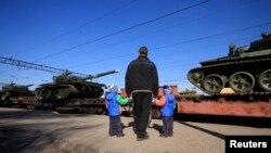Акмәчет янындагы Гвардейское касабасында бер ир кеше балалар белән гаскәр килүен күзәтә