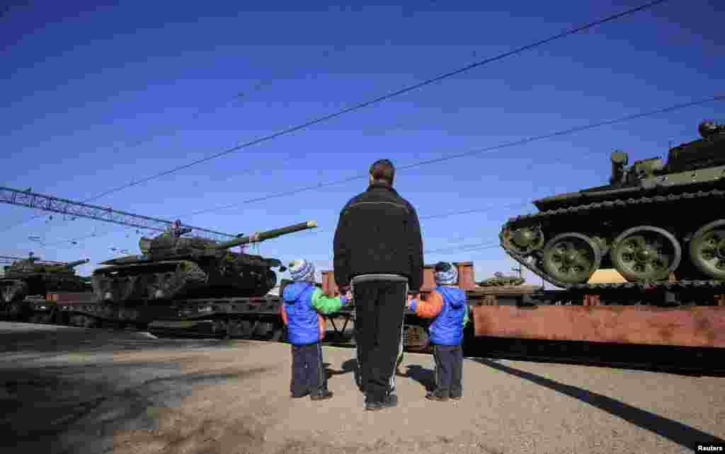 Erkek ballarınen beraber Qırımğa kelgen rus tanklarına baqp otura. Sarabuz qasabası, mart 31 künü 2014 senesi