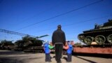 Балаларын жетектеген Қырым тұрғыны Ресей танкілеріне қарап тұр. Қырым, Гвардейское ауылы, 31 наурыз 2014 жыл.