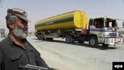 Standing guard near an oil tanker that was allegedly attacked by Taliban militants near the Afghan border in Chaman in July