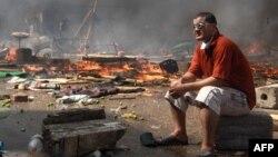 Një demonstrues qëndron i ulur në një nga zonat e Kajros ku janë përleshur forcat e rendit dhe protestuesit islamik, 14 gusht 2013