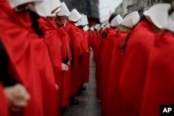 """Активисти, подкрепящи декриминализирането на абортите в Аржентина, на демонстрация пред Конгреса през юли 2018 г. Те са облечени с костюми като тези на жените в """"Историята на прислужницата"""". Тогава Атууд изрази подкрепата си в Туитър."""