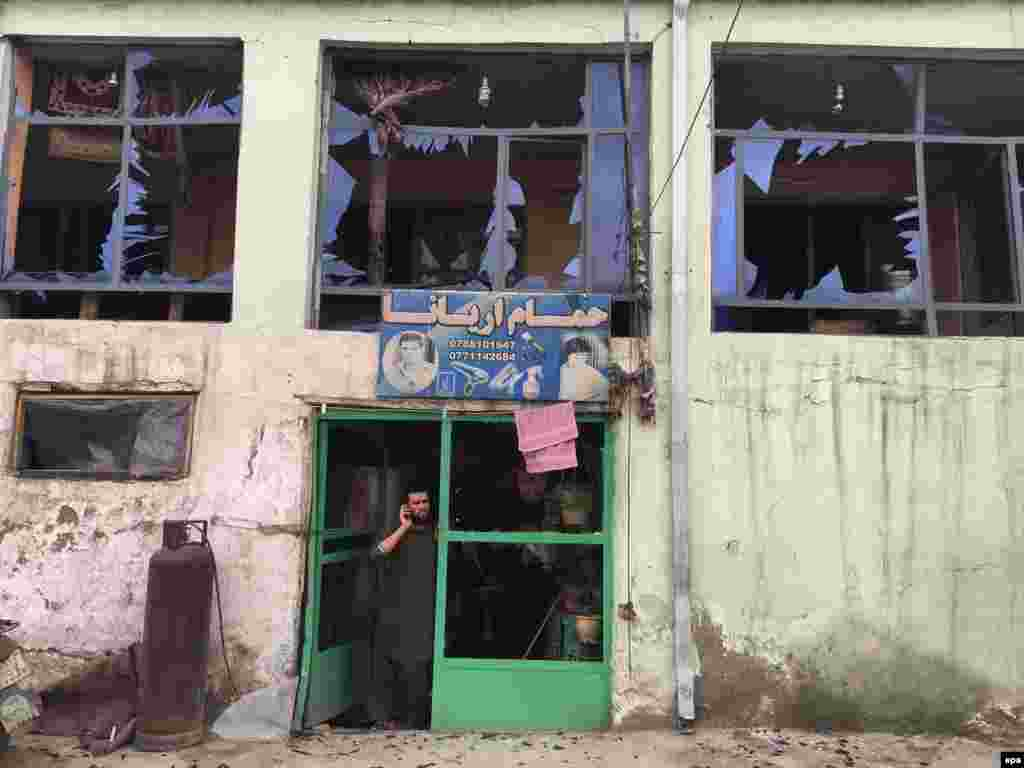 A man stands inside his damaged shop near the scene of the bomb blast.