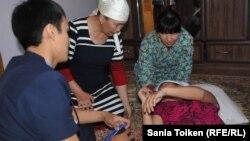 Медик скорой помощи (слева) и родственники школьницы Маусымжан Адильхановой рядом с ней после приступа удушья и недомогания. Село Кызылсай Мангистауской области, 26 марта 2015 года.