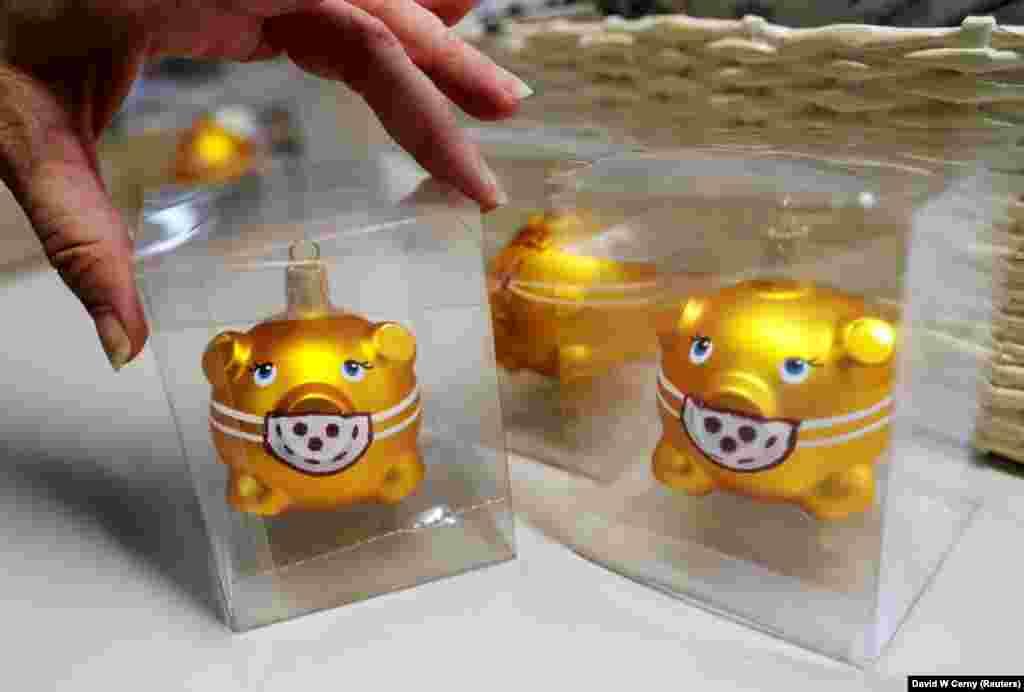 Робітниця упаковує скляні ялинкові іграшки у формі свинок у масках на фабриці OzdobaCZ. Двур Кралове-над-Лабем. Чехія, 1 грудня 2020 року