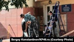 Workers repair damage at the site of a blast outside the national Pension Fund office in Kaluga on August 3.