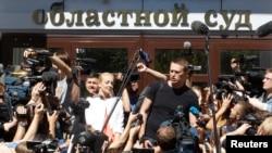 Алексей Навальний ва турмуш ўртоғи Киров област суди биноси олдида журналистлар билан суҳбатлашмоқда.