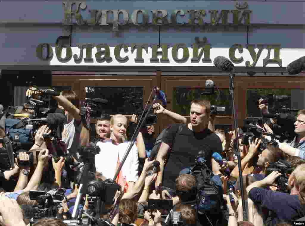 Navalny məhkəmənin binası qarşısına toplaşan tərəfdarları və jurnalistlər arasında. 19 iyul 2013