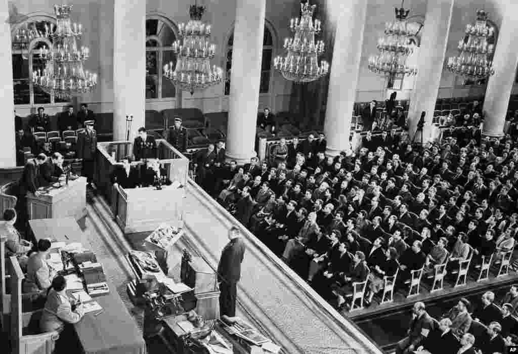 Пауерс сидить на лаві підсудних. Безпосередньо перед Пауерсом стоїть його захисник Михайло Гріньов. На передньому плані зліва судді: три радянських офіцери високого рангу. Прямо перед ними розташоване спорядження, яке, як кажуть, тримав Пауерс у своєму літаку