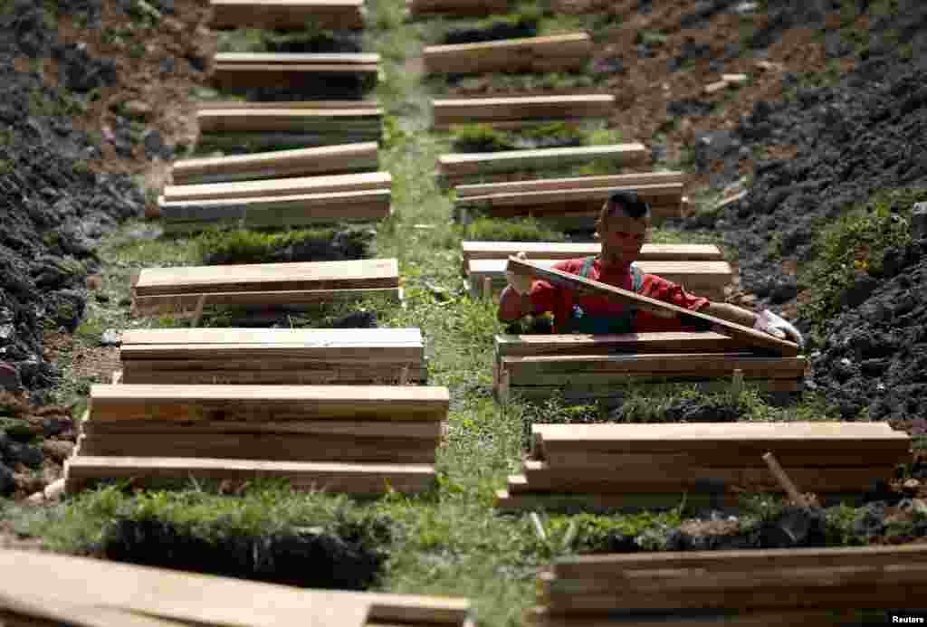A worker prepares graves ahead of a ceremony at a memorial center for the victims of the Srebrenica massacre in Potocari, Bosnia-Herzegovina, on July 7. (Reuters/Dado Ruvic)