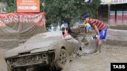 People examine a car damaged by the landslide in Almaty.