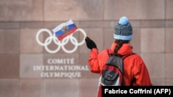 A supporter waves a Russian flag in front the International Olympic Committee headquarters in Switzerland.