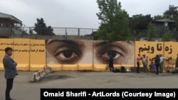 Afghan artist Omaid Sharifi's painting against corruption on a blast wall in Kabul.