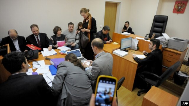 The plaintiffs (rear) and the respondents (front) in a suit against Madonna sit at a table in a courtroom in St. Petersburg on November 22.