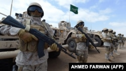 Saudi forces stand to attention during a visit by Yemeni Prime Minister Khaled Bahah at the Saudi-led coalition military base in Yemen's southern embattled city of Aden on September 28.