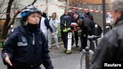 France -- Firefighters carry a victim on a stretcher at the scene after a shooting at the Paris offices of Charlie Hebdo, a satirical newspaper, January 7, 2015.