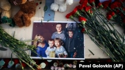 A photo of a young family is surrounded by candles, flowers, and toys during a ceremony commemorating the victims of a fire in a shopping mall in the Siberian city of Kemerovo, in the center of Moscow on March 27.