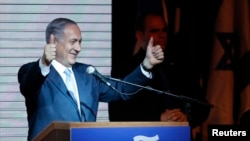 Israeli Prime Minister Benjamin Netanyahu gestures to supporters at party headquarters in Tel Aviv early on March 18.