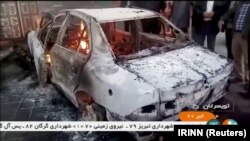 People stand near a burning car in Tuyserkan, Hamadan Province, on December 31.