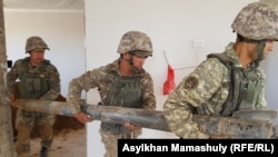 Military workers clear debris in the aftermath of the explosion in Arys, a small town in the Turkestan region, in June 2019.