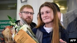 Maria Butina, who served nine months in a U.S. prison for acting as a Russian government agent, arrives at Moscow's Sheremetyevo airport on October 26, a day after her release.