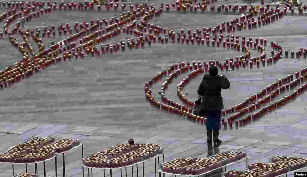 A woman prays as she takes part in a mourning ceremony on Independence Square in Kyiv. Ukraine held a day of mourning for the 13 people killed on January 13 when a passenger bus came under heavy fire in eastern Ukraine. (Reuters/Gleb Garanich)