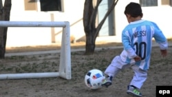 Afghan boy Murtaza Ahmadi, a young fan of FC Barcelona's Argentinian striker Lionel Messi, controls the ball while wearing an Argentinian national soccer team jersey signed by Messi in Kabul in February.