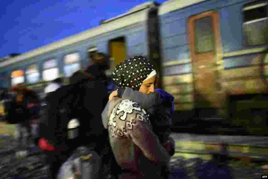 Мигранты и беженцы садятся в поезд на границе Македонии и Греции, чтобы отправиться в Сербию, 20 октября 2015 г.