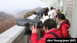 La granița cu Coreea de Nord, turiștii se uită de partea cealaltă a frontierei, din clădirea Unification Observation Post din Paju