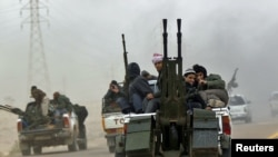 Rebel fighters flee from Ajdabiya on the road to Benghazi on March 15.