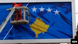 A worker fixes the national flag of Kosovo to a billboard ahead of Kosovo's fifth anniversary of its independence in Pristina in February 2013.