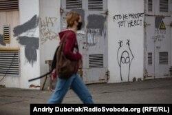 Дівчина проходить повз трансформаторну будку з графіті «Хто не працює, той не їсть»