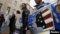 Demonstrators stand outside the Moscow office of the Golos election-monitoring NGO, with one sign branding the group a U.S. agent.