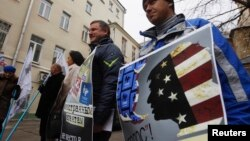 """Russian protesters outside the office of the election-monitoring NGO Golos in Moscow accuse the group of foreign ties. Rodger Potocki says the NED doesn't """"ascribe to this idea that there are phrases or approaches that are foreign or domestic, that are internal or external."""""""