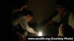 Өзбекстан -- Электр энергиясы жок маалда шам жагып отурган үй-бүлө.