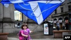 На улице Абердина девочка с флагом сторонников независимости Шотландии
