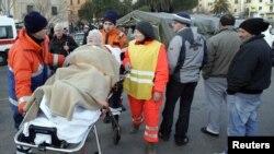 Спасувачите и помагаат на една преживеана жена.