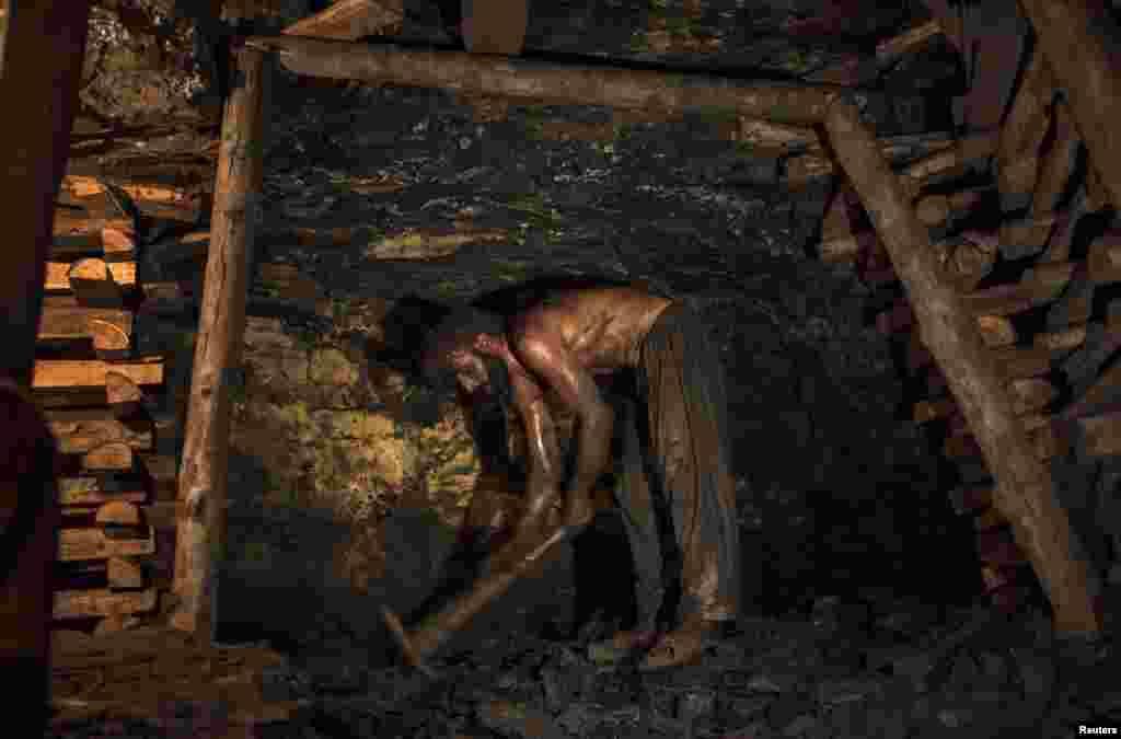 Zamurud Khan breaks coal with a pickax.