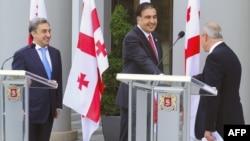 Վրաստան - Նախագահ Միխեիլ Սահակաշվիլին սեղմում է նորանշանակ վարչապետ Վանո Մերաբիշվիլիի ձեռքը` նախկին վարչապետ Նիկա Գիլաուրիի ներկայությամբ կայացած արարողության ժամանակ, Թբիլիսի, 1-ը հուլիսի, 2012թ.