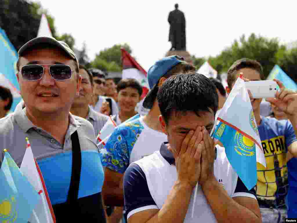 Supporters of Almaty's candidacy for the 2022 Winter Olympic Games react after the announcement that Almaty had been eliminated from the International Olympic Committee's voting process to select the host city, in Almaty on July 31. (Reuters/Shamil Zhumatov)