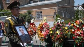 Armenia - A soldier holds the picture of Vahe Avetian during the military doctor's funeral in Yerevan, 02Jul2012.